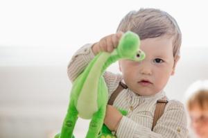 boy-holding-dinosaur-toy-looking-at-camera_23-2147664111