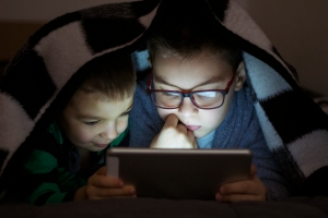 Two kids using tablet pc under blanket at night. Cute Brothers with tablet computer in a dark room smiling